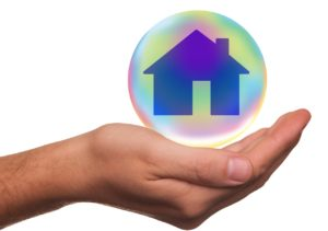 Picture of house in a bubble held by a hand.